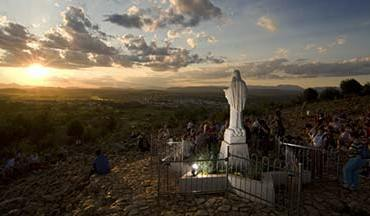 the sunsetting over a statue of the blessed mother in Medjugorje