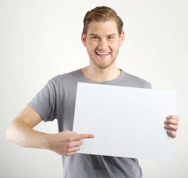 Homem segurando uma placa e apontando pra ela