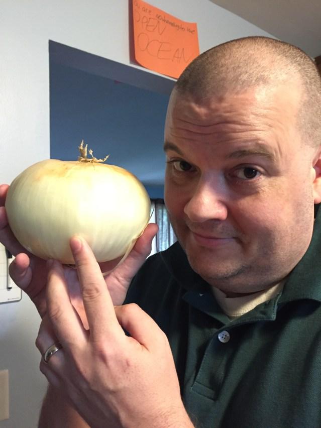 smiling man holding large yellow onion