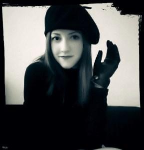 Foto de M. Sardini. A escritora está usando uma boina e luvas de couro. A foto é em preto e branco.
