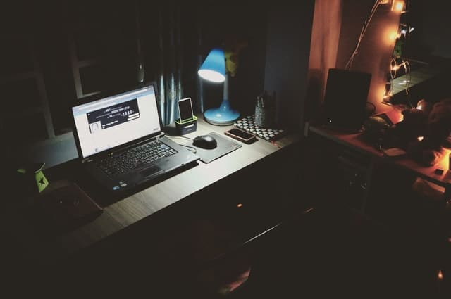 laptop on desk with light on beside laptop.
