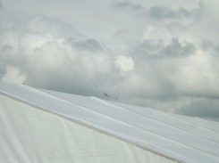 A VIP marquee at Duxford during the Flying Legends airshow matches the angle of the plane's flightpath.