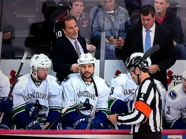 John Tortorella shares a laugh with referee Wes McCauley