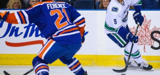 Zack Kassian of the Vancouver Canucks gets a headshot from Andrew Ference of the Edmonton Oilers. (Photo credit: thescore.com)