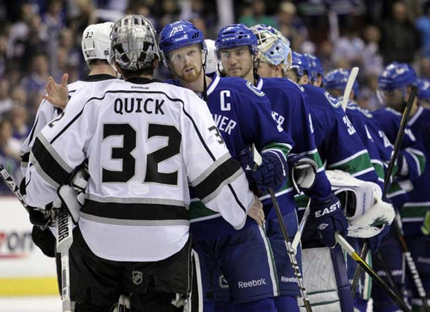Henrik Sedin of the Vancouver Canucks shakes hands with Jonathan Quick of the Los Angeles Kings.