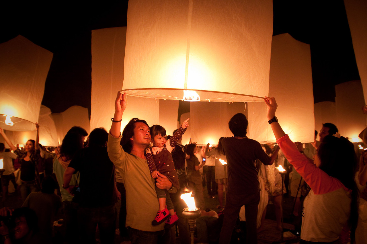 A family lighting their lanterns in Mae Jo for the Lantern Release Ceremony of Loy Krathong 2010