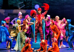"Wesley Allen as Sebastian (center), Kathleen Rooney as Ariel (left center), and the ensemble of ""The Little Mermaid"". Photo 