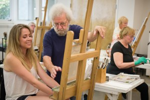 Instructor Bud Deihl helps an oil painting student during one of the many classes offered at Valley Art Center. Photo by Valley Art Center / Michael Steinberg