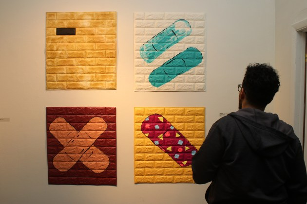 """A viewer takes in all four components of """"Philanthropic Patchwork"""" during the opening reception for Martinez E-B's """"B Side"""" Oct. 5 at Waterloo Arts in Cleveland."""