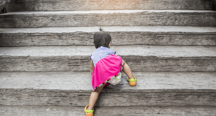 Infant crawling up concrete steps
