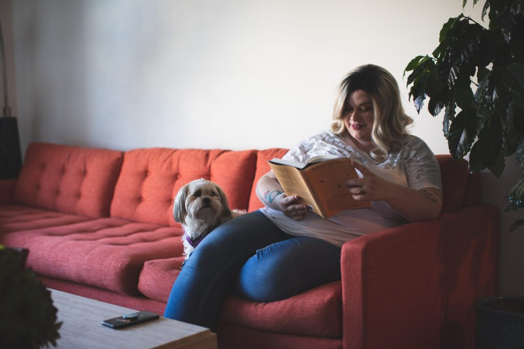 woman-reading-book-on-couch-with-dog