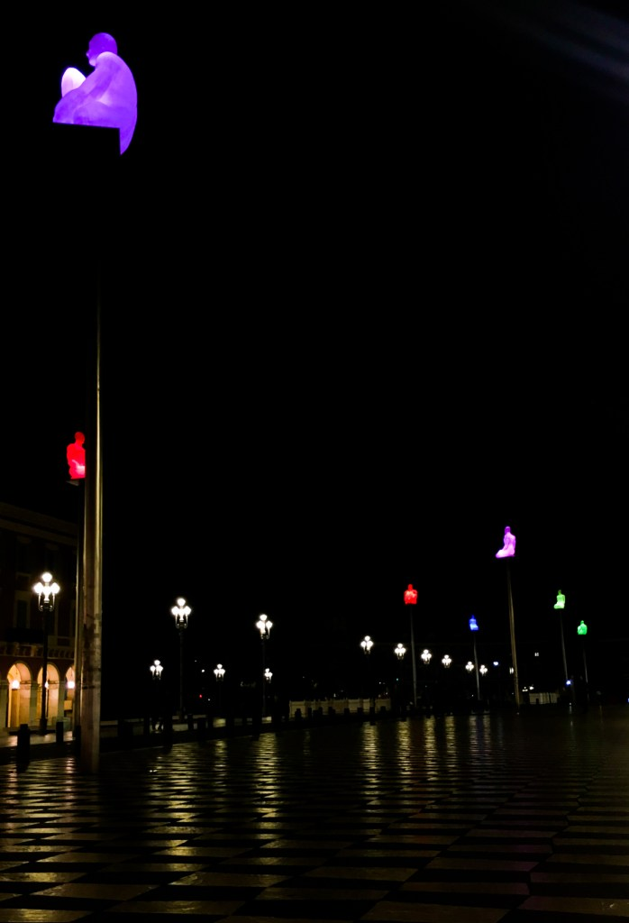 Resin statues lit up at night in Place du Massena