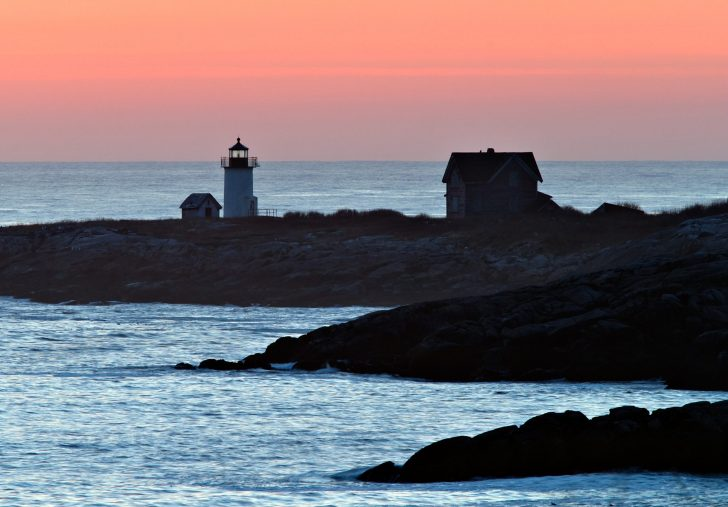 The sun begins to come up on the horizon with the lighthouse on Straitsmouth Island in Rockport MA. in the foreground.