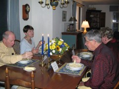 Four people seated at dinner table eating catered food