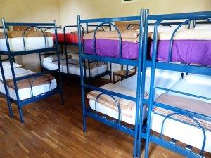 Several metal frame bunk beds in a dorm room