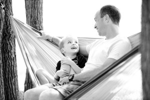 A father and a son sitting in a hammock.