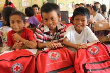 """September 3, 2015. Tolosa, Leyte, Philippines Children from Tanghas Elementary School show off their new Red Cross backpacks. The students continue to enjoy their school, repaired with funds from the American Red Cross in 2014 in partnership with the Spanish Red Cross. Children received backpacks full of supplies to start the school year. The Red Cross installed hand water pumps, constructed six new latrines, and repaired classrooms that were badly damaged by Typhoon Haiyan. Even though it was ravaged by high winds and fallen coconut trees, about 20 families used the school as a shelter in the aftermath of the typhoon. One hundred and thirty-two students, from kindergarten to sixth grade, attend Tanghas Elementary School. The school's five teachers all survived the storm and returned to teach this year. All the surrounding schools are full, so if this one wasn't able to reopen, they'd have nowhere else to get their education. The Red Cross trains local people on carpentry, plumping, electrical and construction skills and then pays them to repair schools like Tanghas Elementary. """"Without the Red Cross repairing the school, I don't know what would happen to our children,"""" said school official, Noresita A. Go. This project is in collaboration with the Spanish Red Cross. Photo by Niki Clark/American Red Cross"""