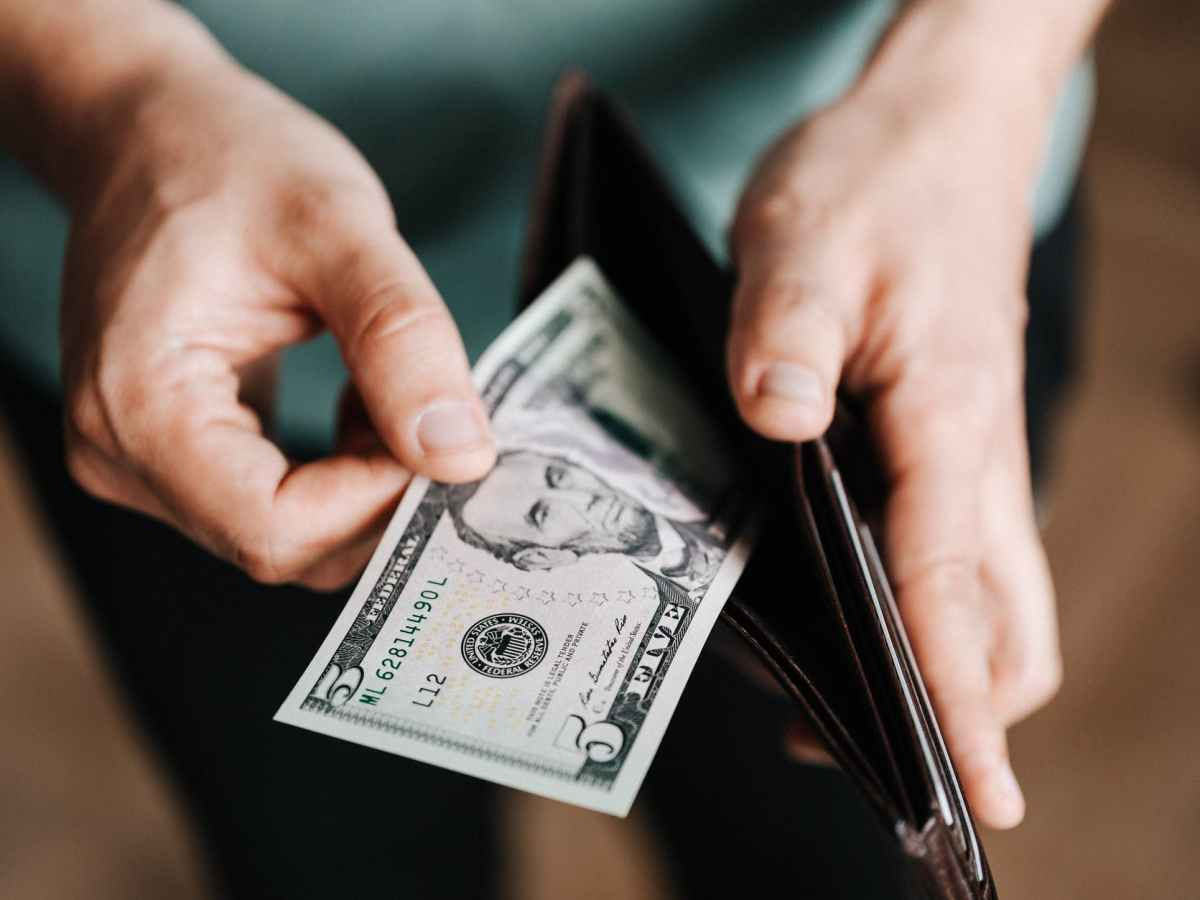 unrecognizable man holding wallet with money