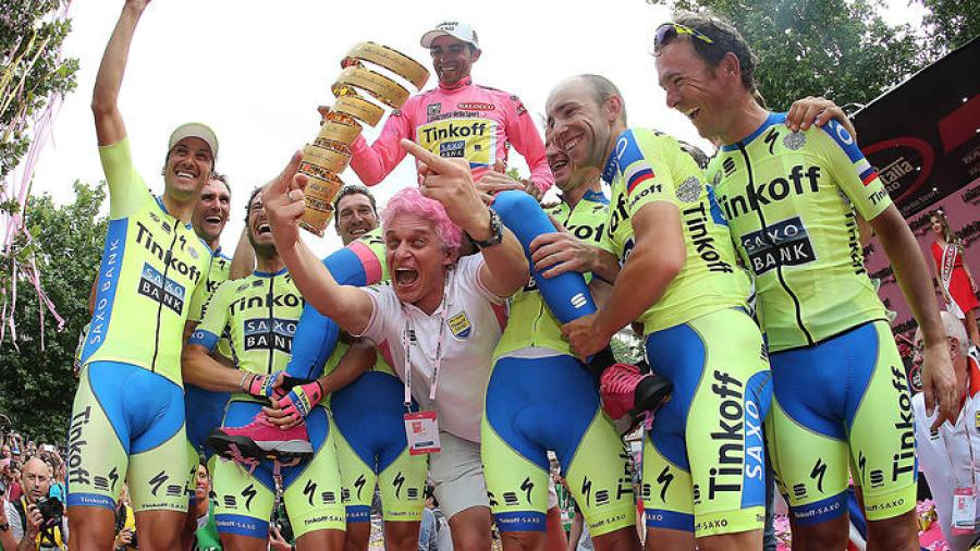 Spain's Alberto Contador (C, up) celebrates with his trophy, flanked by his Tinkoff-Saxo teammates and Russian businessman and team sponsor Oleg Tinkov (C), on the podium after winning the 98th Giro d'Italia, Tour of Italy, in Milan on May 31, 2015. AFP PHOTO / LUK BENIES (Photo credit should read LUK BENIES/AFP/Getty Images)