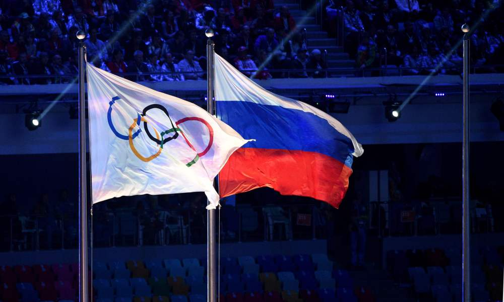 (FILES) This file photo taken on February 23, 2014 shows an Olympic Games flag and a Russian flag waving during the closing ceremony of the winter Olympics in Sotchi. Russia operated a state-dictated doping system during the 2014 Sochi Winter Olympics and other events, an independent investigator said today in a report likely to lead to demands for Russia to be completely banned from the Rio Games. / AFP PHOTO / ANDREJ ISAKOVICANDREJ ISAKOVIC/AFP/Getty Images ORIG FILE ID: 554107150