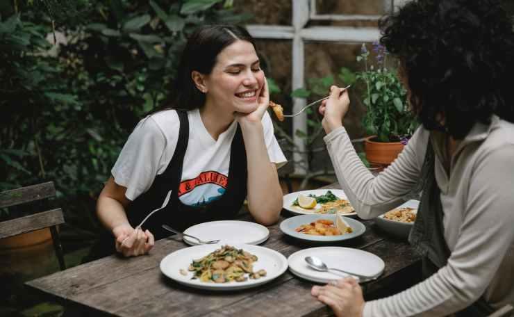 woman feeding girlfriend with fried seafood in garden