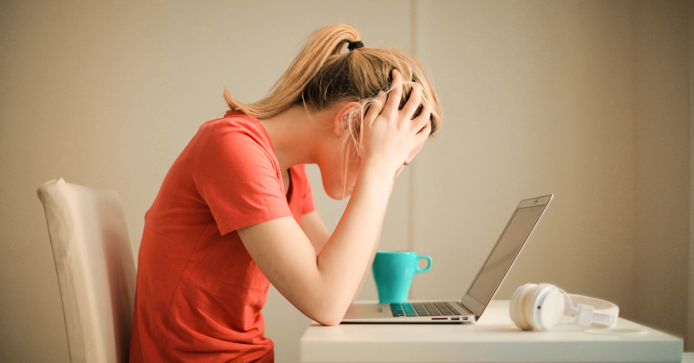 stressed out young woman looking at laptop