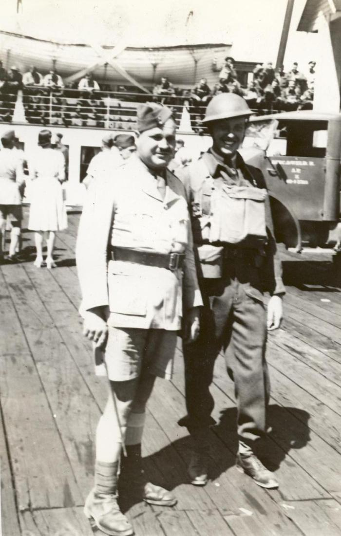 Two officers standing in uniform on the dock. Army ttruck behind them Officer on right with helmet and respirator (gas mask) etc. On the dock at Nanaimo. With the Lincoln and Welland Regiment on the dock at Nanaimo, British Columbia circa 1942 - Lieutenant A. H. Stevens on the right.