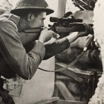 British sniper aiming his sniper rifle through a hole in the wall of a building.