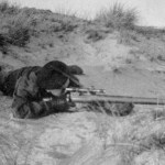 British sniper training among sand dues, lying in a prone position.