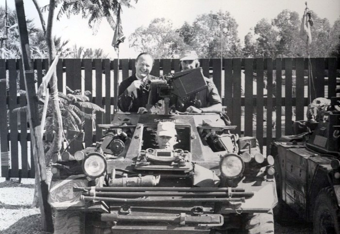 Front view of a Ferret Scout Car with three men in it.