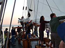 Lowering the main sail is almost an all hands operation on the Schooner Adventuress