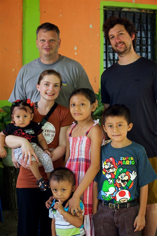 Derrick, Marshalll and Tessa are standing beside Pastor Damiàn, along with many children in the community that come to his home for food.