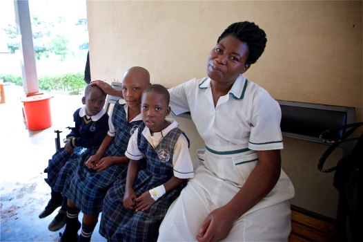 School nurse Namulinde Rebecca sitting beside the other three children who were very fortunate to escape the accident with minor wounds