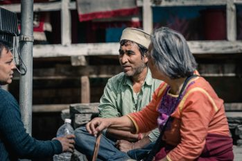 Auntie conversing with those she serves in Malana village