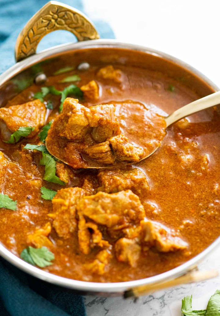 Spoon holding a piece of lamb over a bowl of lamb curry