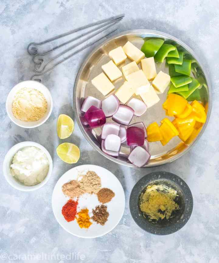 All Ingredients for making paneer tikka laid on a grey board