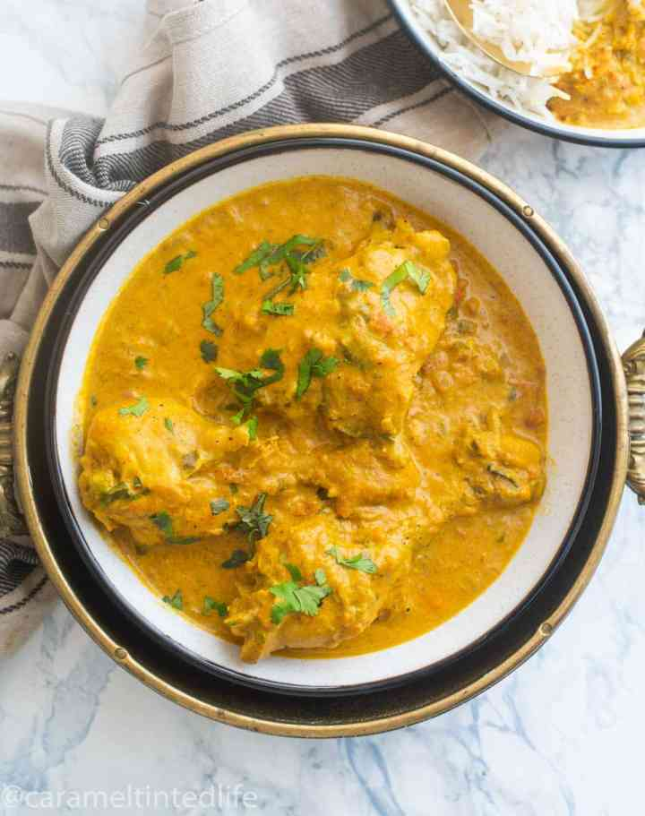 Chicken drumsticks in a curry sauce served in a white bowl against a white backdrop, with a tea towel on the side
