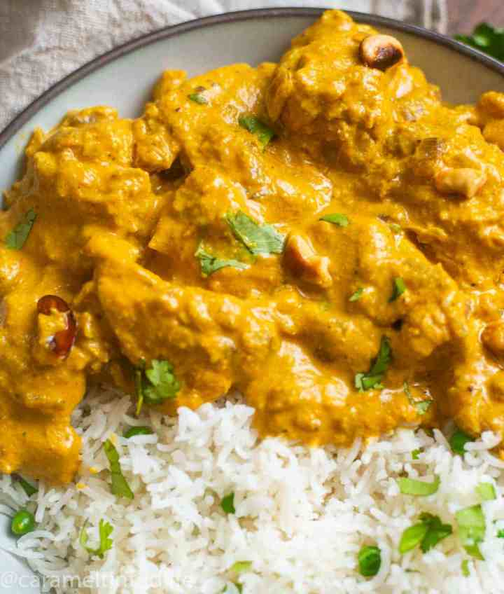 Close-up of chicken korma in a bowl with rice and chopped cilantro garnish