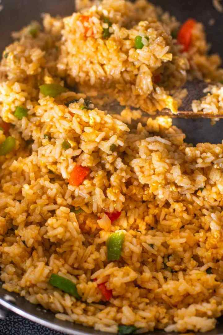 Fried rice being tossed in sauces in a wok