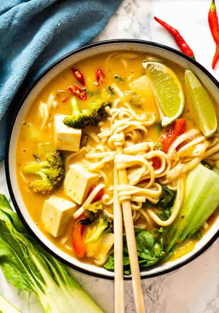 Top-view of a bowl of noodle soup with chopsticks and bok choy in the background