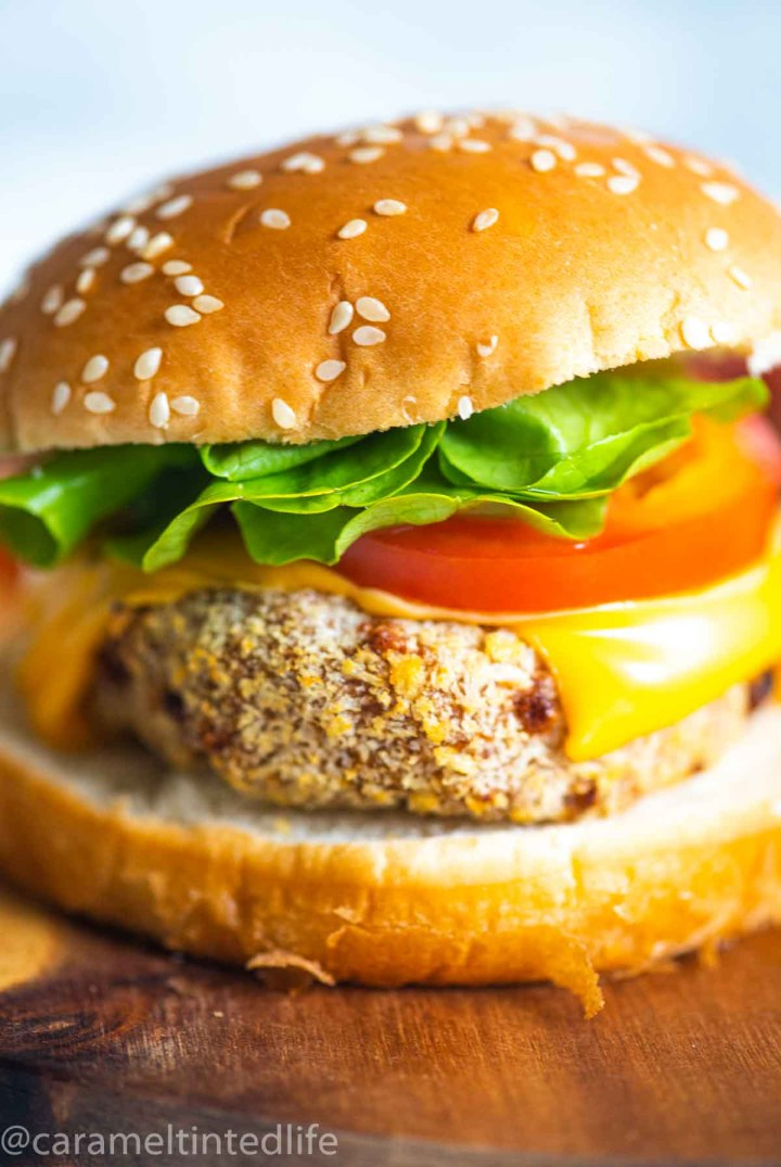 Close up of a chicken burger on a wooden surface
