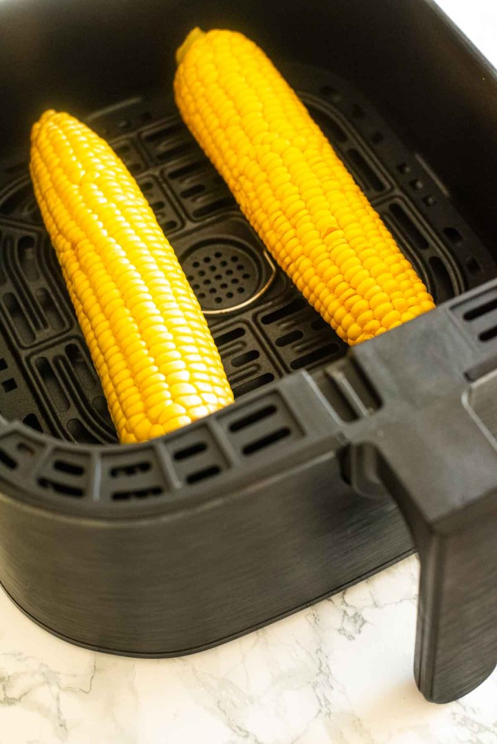 Two corn on the cobs in an air fryer
