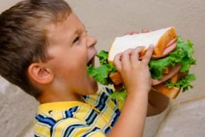 Boy Eating Huge Sandwich --- Image by © Dean Muz/Design Pics/Corbis