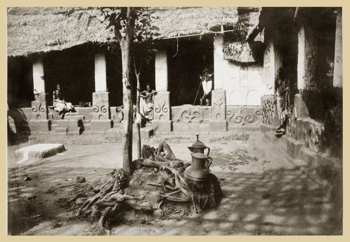 Courtyard in either the royal mausoleum or in the palace of the King of Asante, where The Asante Jug (Richard II Ewer) can be seen, ca. 1887. The National Archives of the UK, ref. CO1069/31(7). Photographer unknown Resting beneath a tree, two late fourteenth-century English jugs taken from Kumasi by the British at the end of the nineteenth century. We do not know when or how they arrived in the Asante capital. It is possible they traveled across Saharan trade routes as early as the fifteenth century; however, it is more probable that they were given as gifts to a local ruler by Europeans trading on the Gold Coast at a later period, witnesses to the shift from desert to coastal trade. The image was taken by an anonymous photographer around 1887, in a courtyard in either the royal mausoleum or in the palace of the King of Asante.