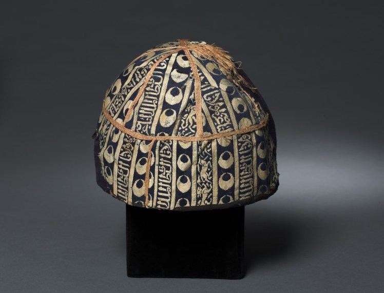 """Cap with striped inscribed silk. Egypt or Syria, Mamluk period, probably sultanate of al-Nasir al-Din Muhammad (reigned 1293–1341, with two interruptions), 14th century. Lampas fabric, silk. Cleveland Museum of Art, Cleveland, OH, purchase from the J.H. Wade Fund, 1985.5. During his sojourn in Cairo, Mansa Musa was received by the sultan al-Nasir al-Din Muhammad, who showered him with gifts including a skullcap with caliphal emblems. The cap undoubtedly resembled this luxurious example, which is inscribed """"Glory to our lord sultan al-Malik al-Nasir."""""""