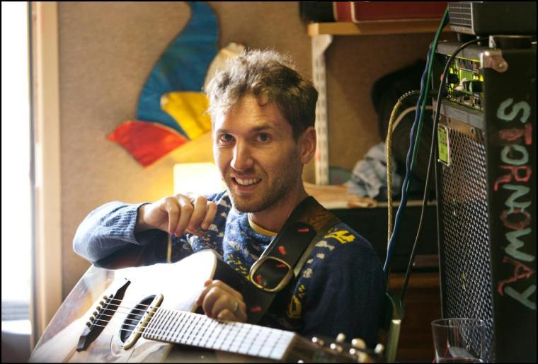 Brian Briggs holding a guitar, smiling.