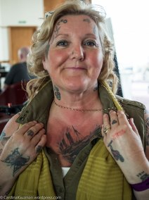 Awesome, tattooed grandma, showing off a Titanic tattoo on her chest.