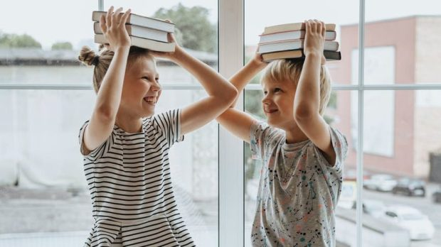 two children with books on their heads and smiling