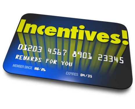 Incentives word on a blue credit or gift card for rewards or bonus savings for buying or special performance achievement