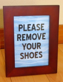 Remove Your Shoes Sign on Blue Waves